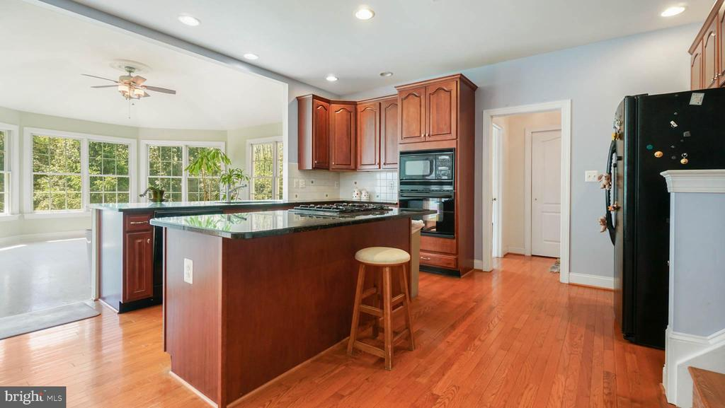 Kitchen off sunroom with picture view of wood - 42531 LONGACRE DR, CHANTILLY