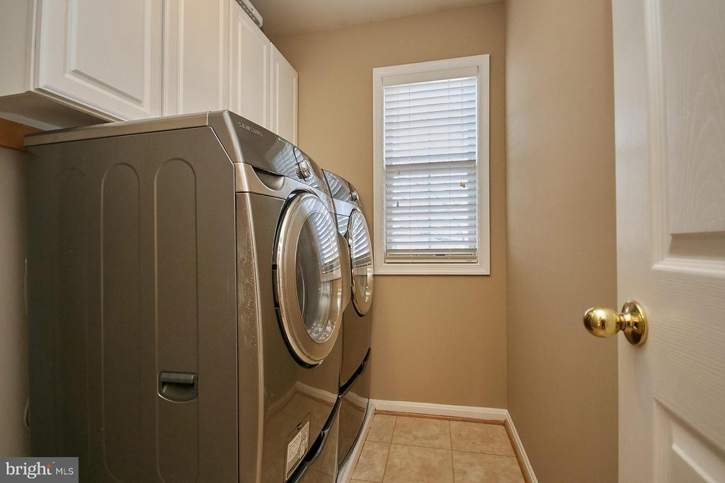 Upper level laundry room with built in cabinetry - 8397 CLEVELAND BAY CT, GAINESVILLE