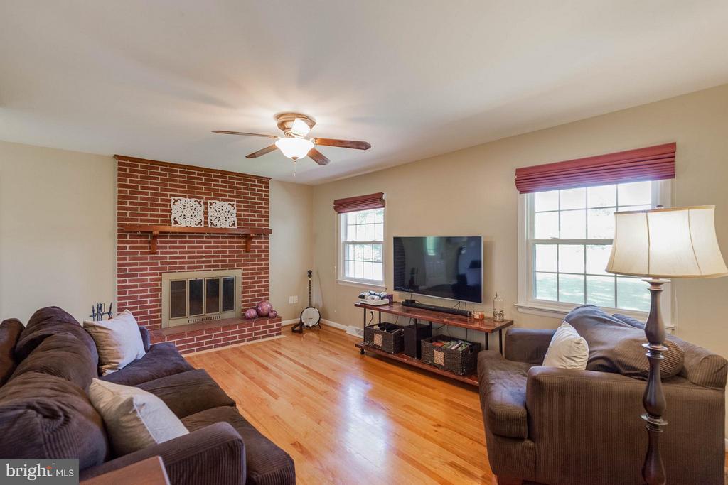 Living Room boasting brick wood FP/mantel - 5719 MOUNT PHILLIP RD, FREDERICK