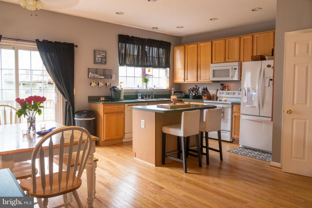 Open kitchen with island and hardwood flooring - 4497 TORRENCE PL, WOODBRIDGE
