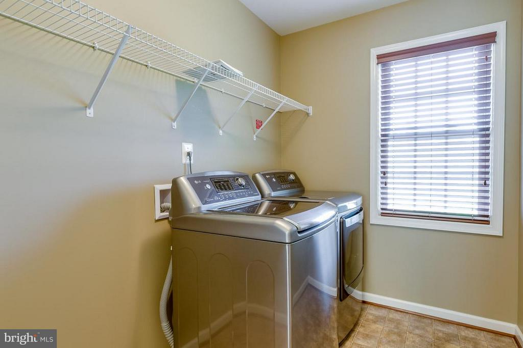 Convenient upstairs laundry room with ceramic tile - 23221 FALLEN HILLS DR, ASHBURN