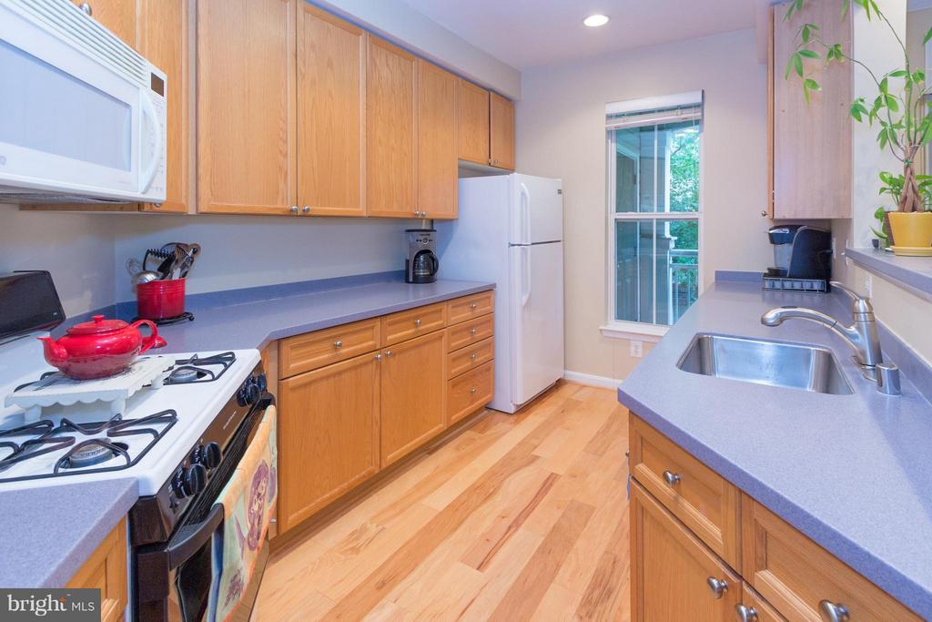 Plenty of Corian counter space and wood cabinets. - 5112 DONOVAN DR #203, ALEXANDRIA