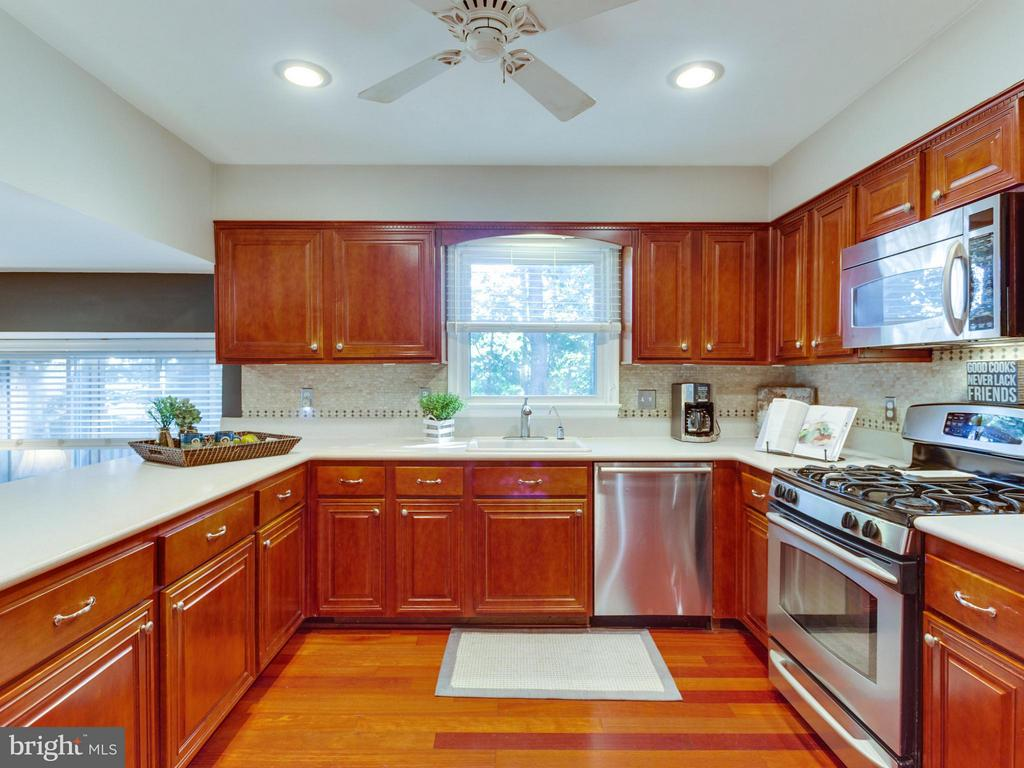 Large kitchen with rows of caramel hued cabinets - 6229 GENTLE LN, ALEXANDRIA