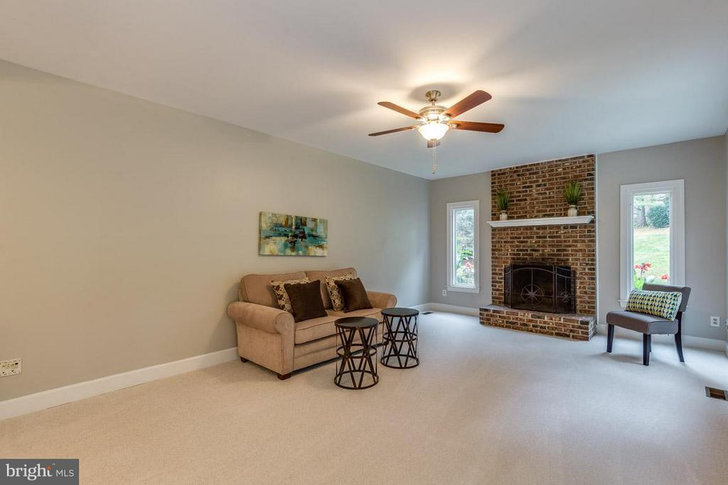 The wood-burning fireplace centers the room - 12105 METCALF CIR, FAIRFAX