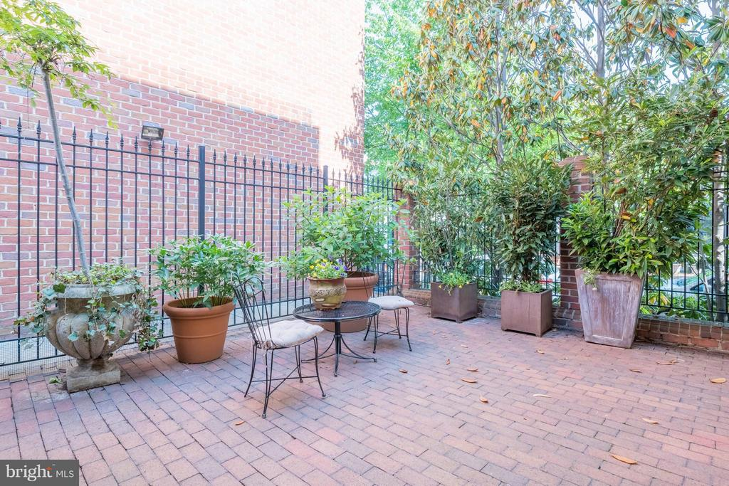 A brick patio with mature plantings offer privacy - 130 COLUMBUS ST N, ALEXANDRIA