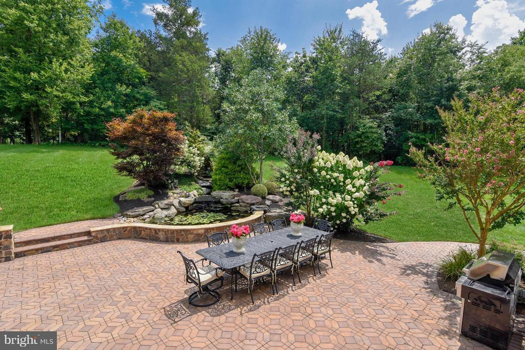Stone Patio featuring koi pond. - 27744 PADDOCK TRAIL PL, CHANTILLY