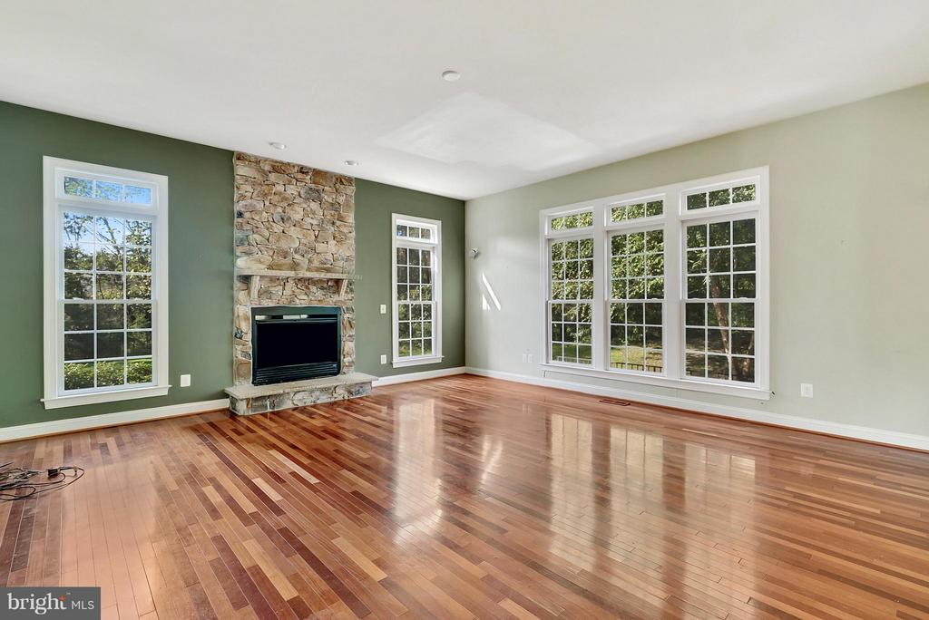 Living room with stone fireplace - 27429 BRIDLE PL, CHANTILLY