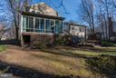 The backyard with deck and sunroom addition. - 11657 GILMAN LN, HERNDON
