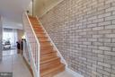 Attractive brick foyer wall and hardwood stairs - 4933 CASIMIR ST, ANNANDALE
