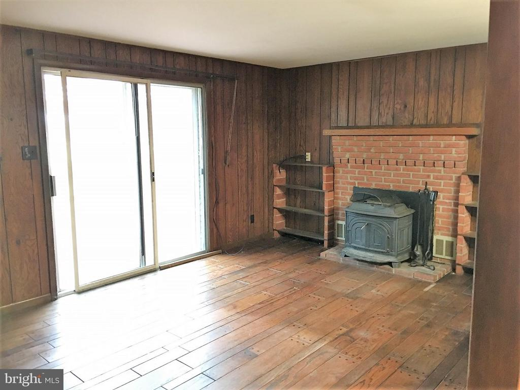 Family room with wood stove and walk out to deck - 7115 DAMASCUS RD, GAITHERSBURG