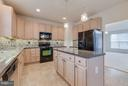 Chef's kitchen with granite countertops - 15004 LUTZ CT, WOODBRIDGE