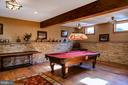 Billiards area with stone wall and wood beams. - 5862 SADDLE DOWNS PL, CENTREVILLE