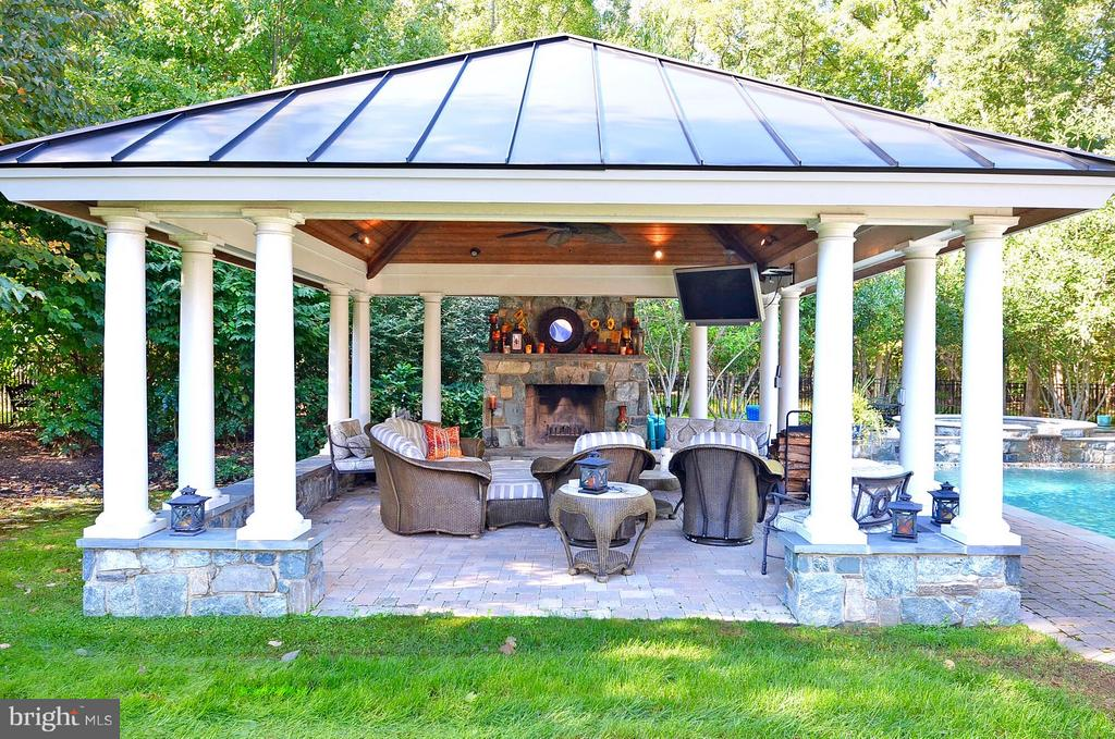 Outdoor room with stone fireplace, views of pool. - 5862 SADDLE DOWNS PL, CENTREVILLE