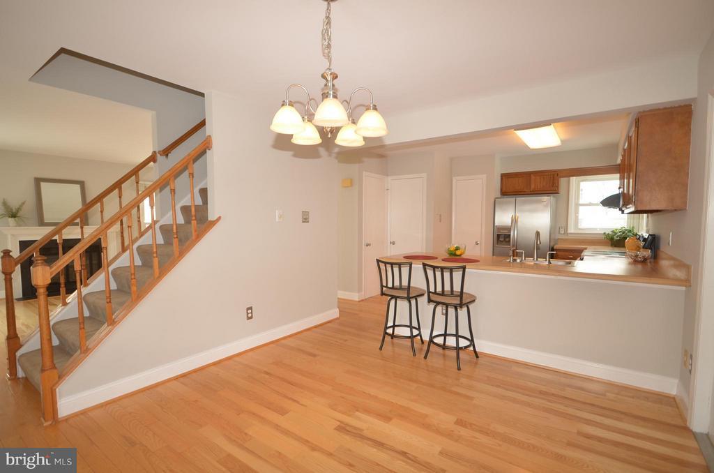 Hardwood floor dining area with breakfast bar. - 14609 BATAVIA DR, CENTREVILLE