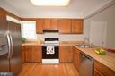 Hardwood floor and earth tones kitchen. - 14609 BATAVIA DR, CENTREVILLE