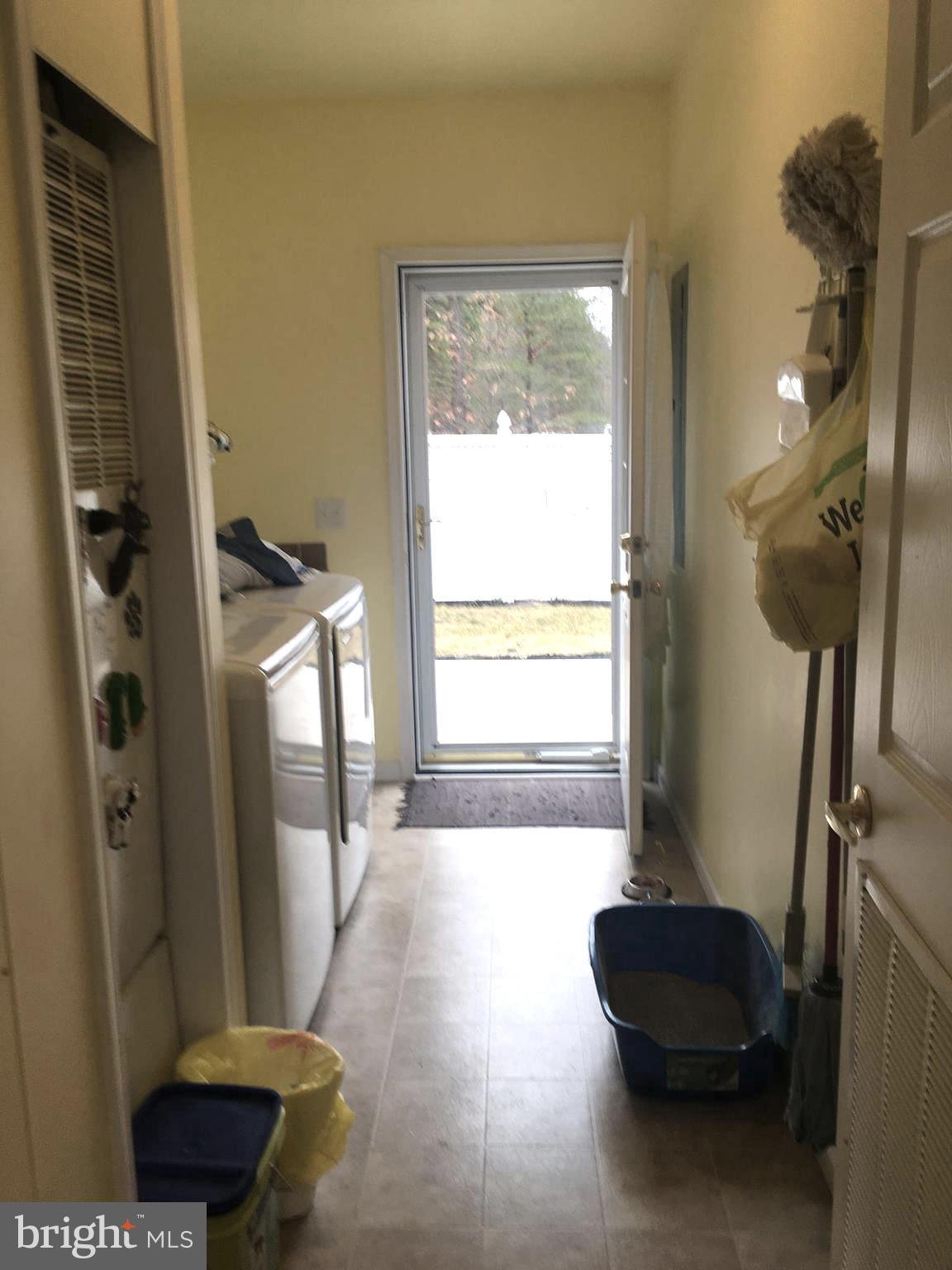 Cheerful laundry room with backyard access & tub