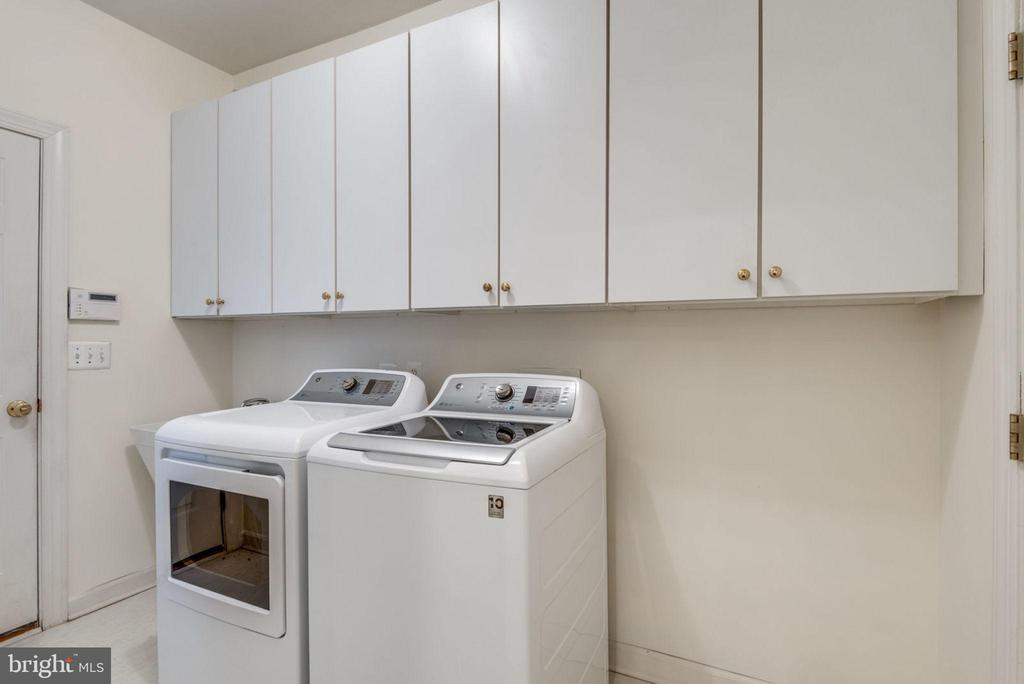 Laundry room with cabinets and a washtub - 18403 KINGSMILL ST, LEESBURG