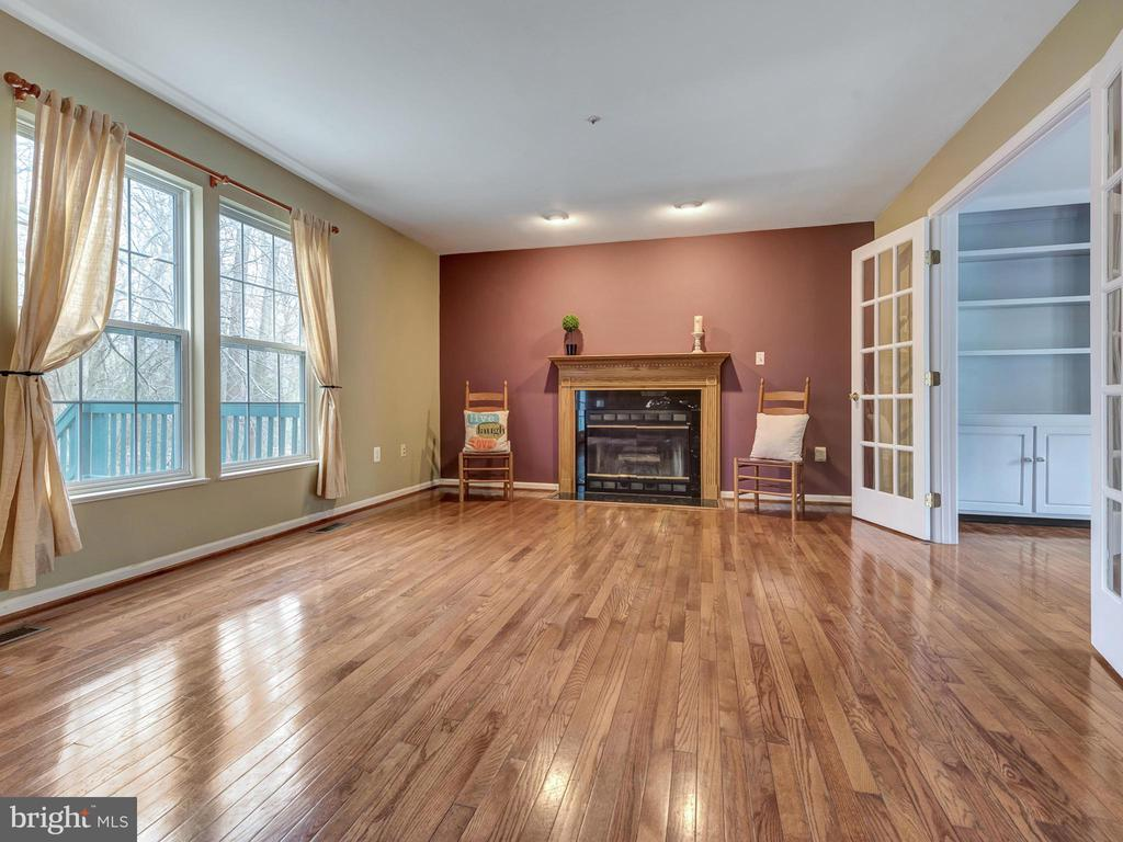 Gleaming hardwood floors in great room with FP - 6012 CREST PARK DR, RIVERDALE