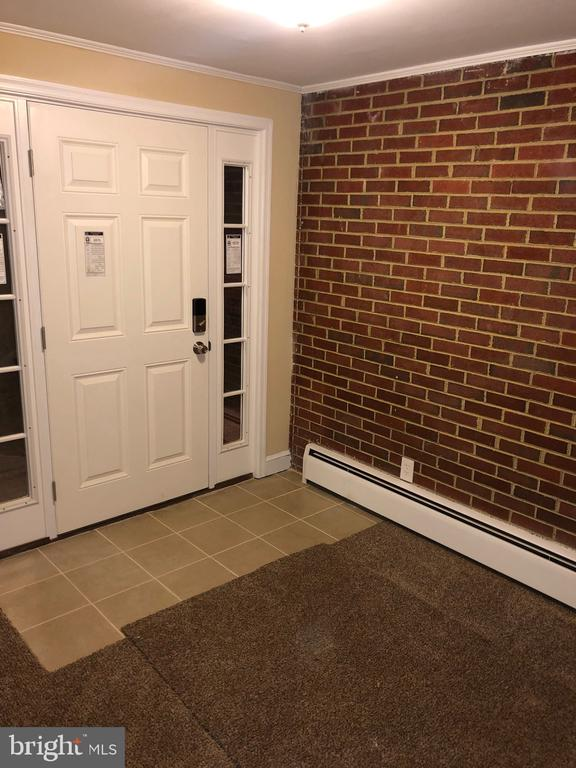 New front door with exposed brick wall at entrance - 5008 BRAYMER AVE, SUITLAND