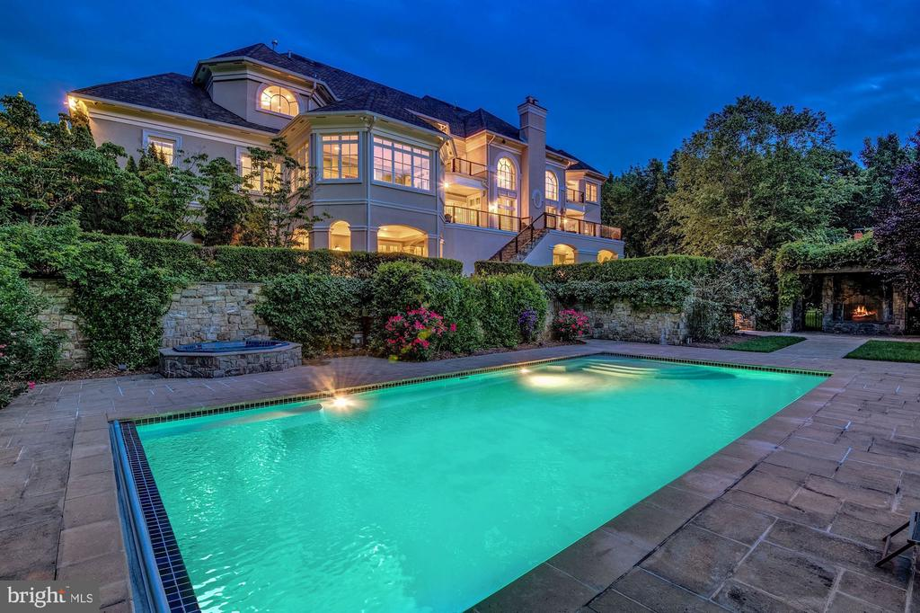 Night view of Pool/spa stone fireplace - 886 CHINQUAPIN RD, MCLEAN
