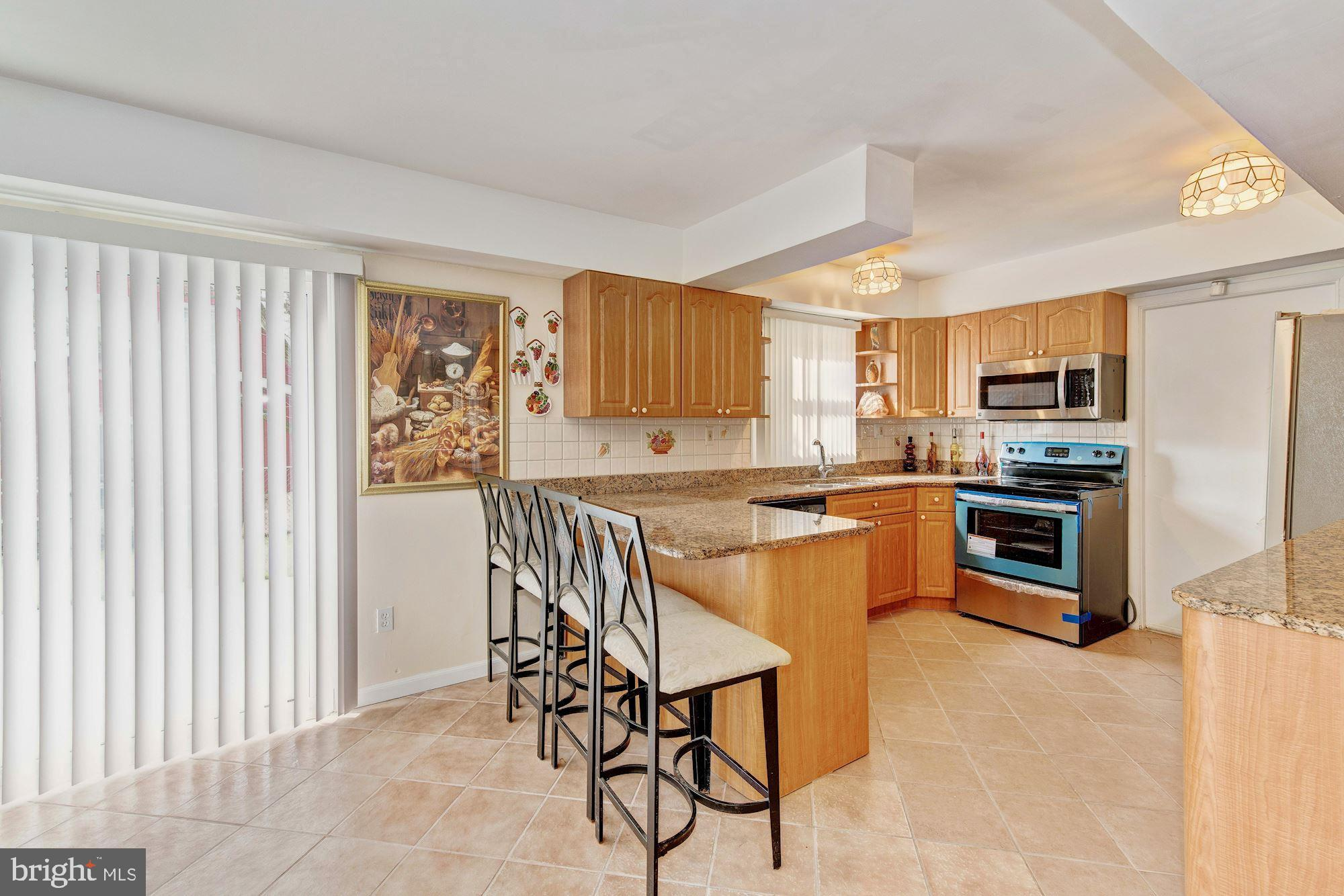Kitchen w/ceramic floors and sliding door to rear