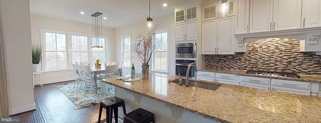 Kitchen with island and tile backsplash - 25532 EMERSON OAKS DR, ALDIE
