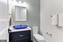 Powder Room with Glass-tiled Accent Wall - 6834 CHURCHILL RD, MCLEAN
