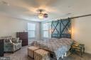 Master bedroom w/ custom barn door headboard - 17040 TAKEAWAY LN, DUMFRIES