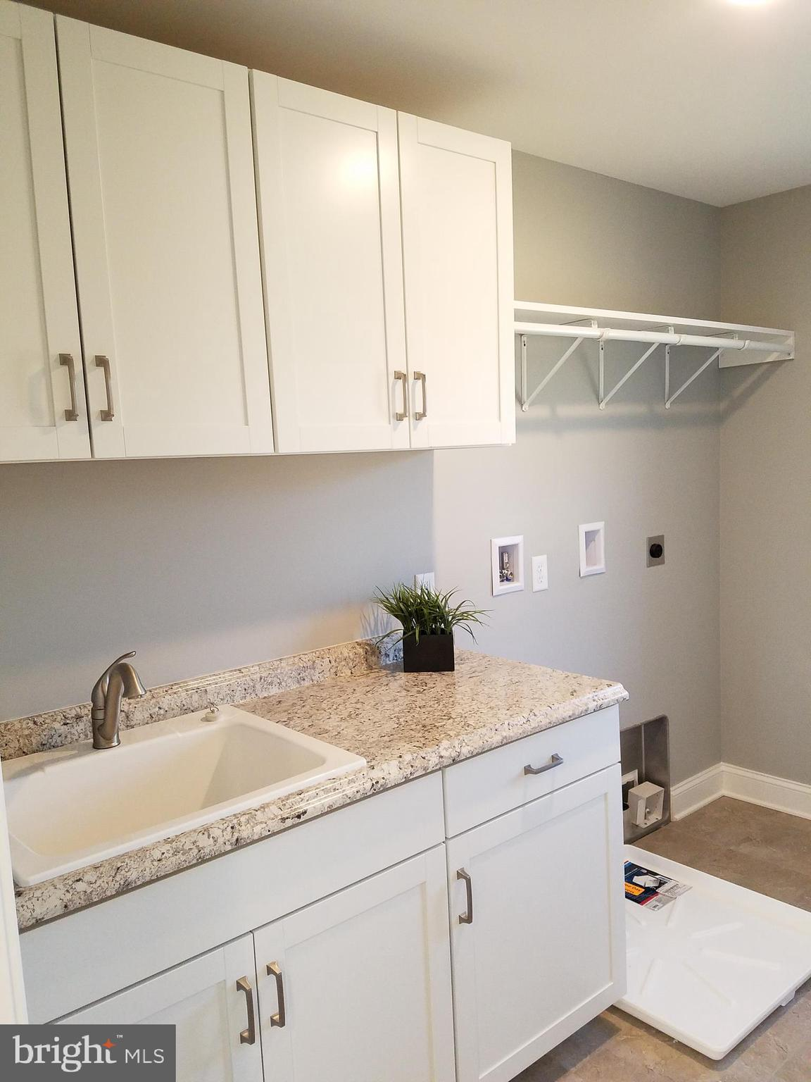 2nd floor laundry w/ sink and cabinets for storage
