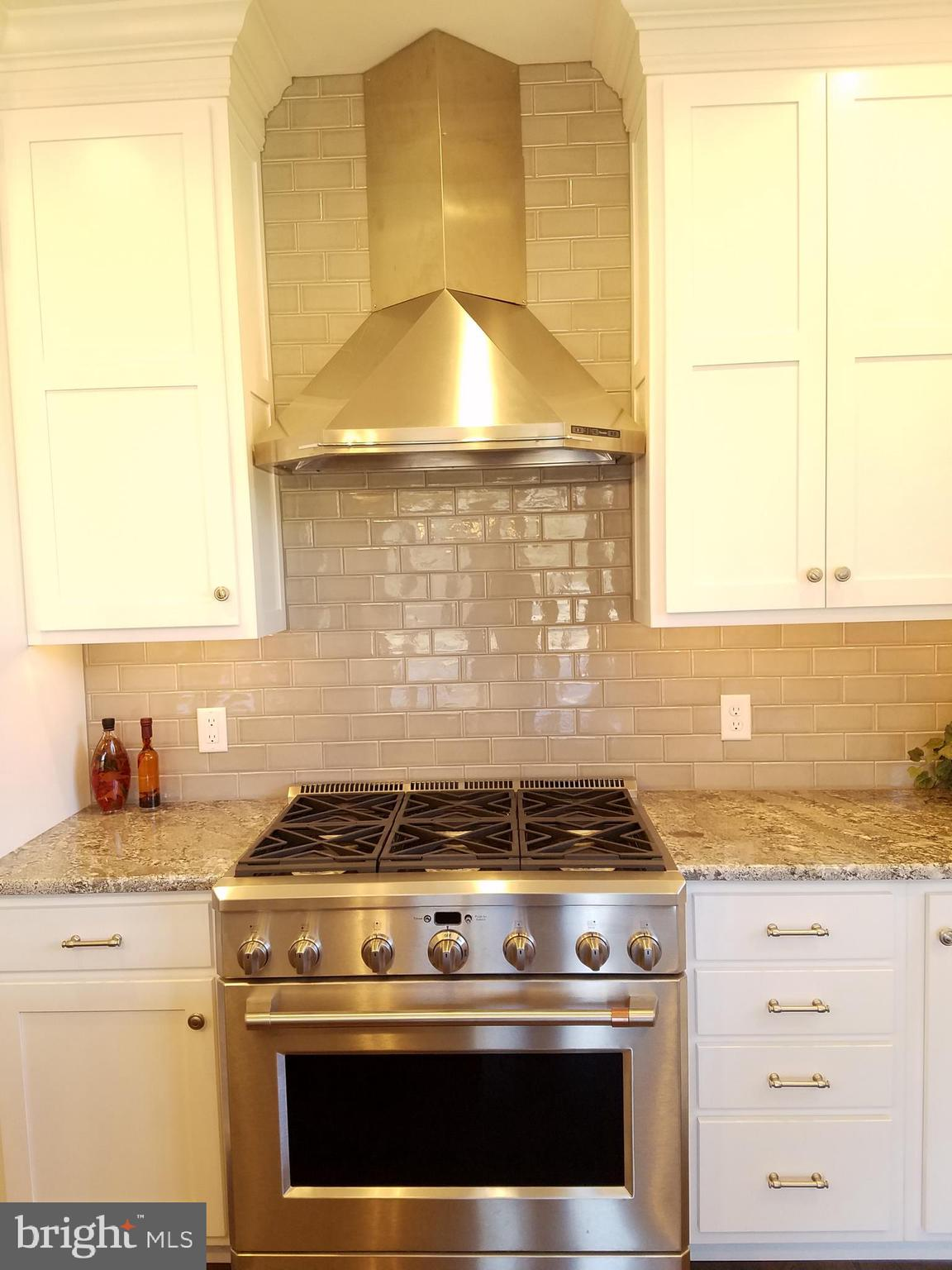 6 burner gas cooktop with tile backsplash.