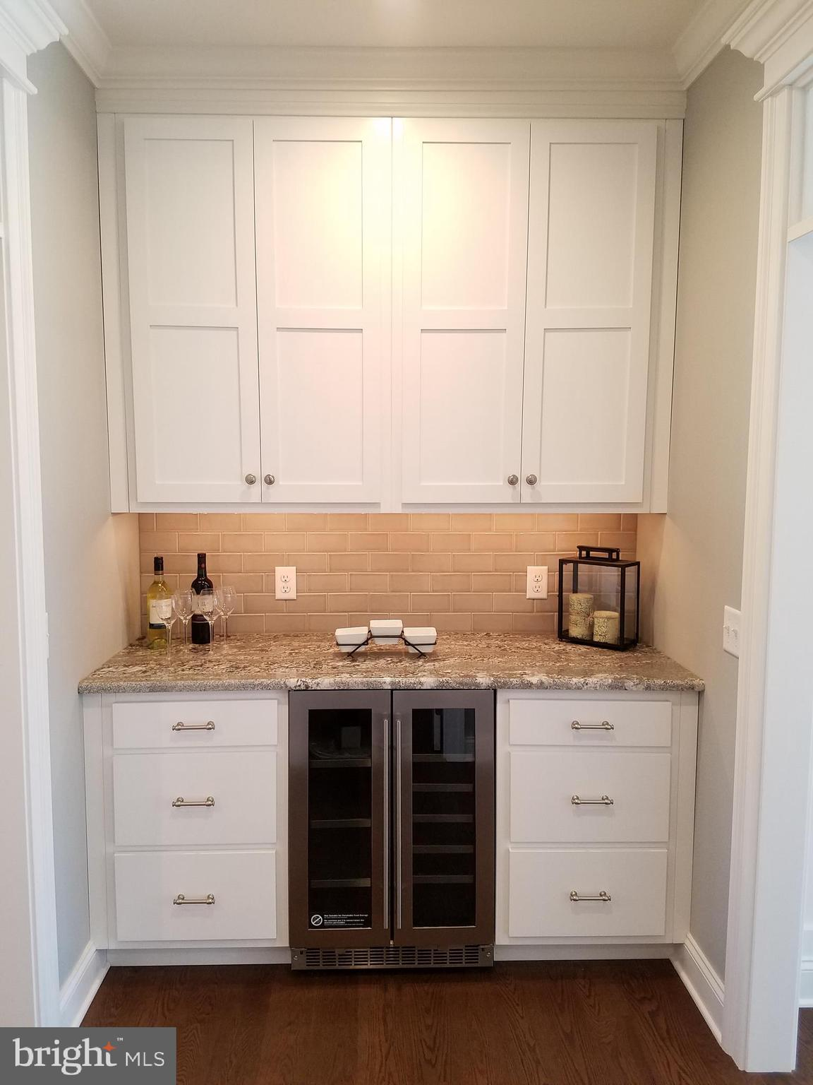 Butler's pantry with wine fridge and granite tops.