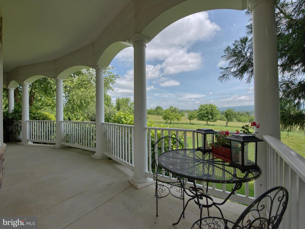 Choose your favorite spot on the wrap around porch - 7803 PICNIC WOODS RD, MIDDLETOWN