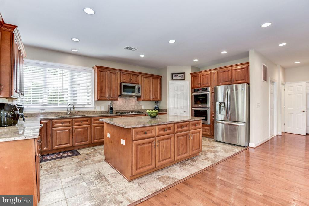 Open kitchen with rich cabinetry and granite ctops - 43345 NICKLAUS LN, CHANTILLY
