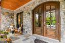 Intimate stone porch w/ arch double wood doors. - 5029 38TH ST N, ARLINGTON
