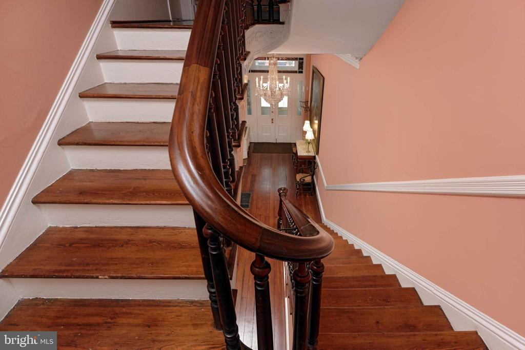 A striking curved staircase  and chair railing - 209 S SAINT ASAPH ST, ALEXANDRIA