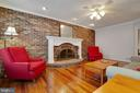 Family room accent wall w wood burning fireplace - 7704 LAKELOFT CT, FAIRFAX STATION