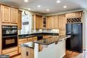 Kitchen island with storage and bar seating - 25647 S VILLAGE DR, CHANTILLY