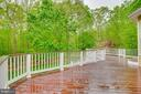 Spacious rear deck overlooks the wooded splendor - 16924 OLD SAWMILL RD, WOODBINE