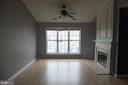 Living room with ceiling fan and cathedral ceiling - 1134 HUNTMASTER TER NE #302, LEESBURG