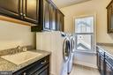 Upper level laundry with sink and~folding counter - 41984 PADDOCK GATE PL, ASHBURN