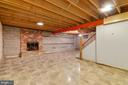 Unfinished basement with wood-burning fireplace. - 15760 OAK LN, HAYMARKET