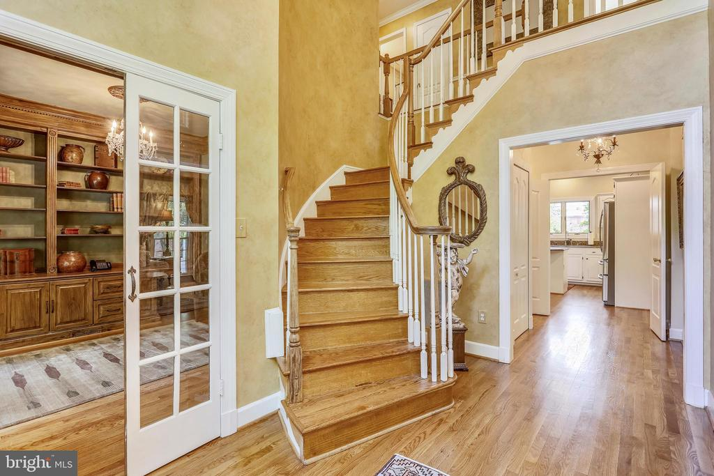 Foyer with curved staircase and hardwood flooring - 11 CLIMBING ROSE CT, ROCKVILLE