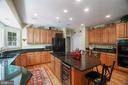 Kitchen features black appliances with wine frig - 12009 BENNETT FARMS CT, OAK HILL