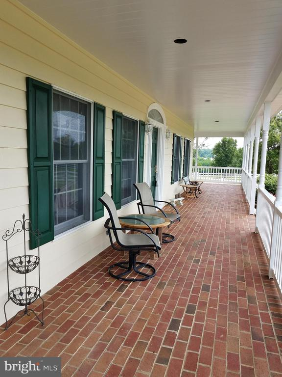 Enter onto the wide brick wrap around porch. - 7411 SNOW HILL DR, SPOTSYLVANIA