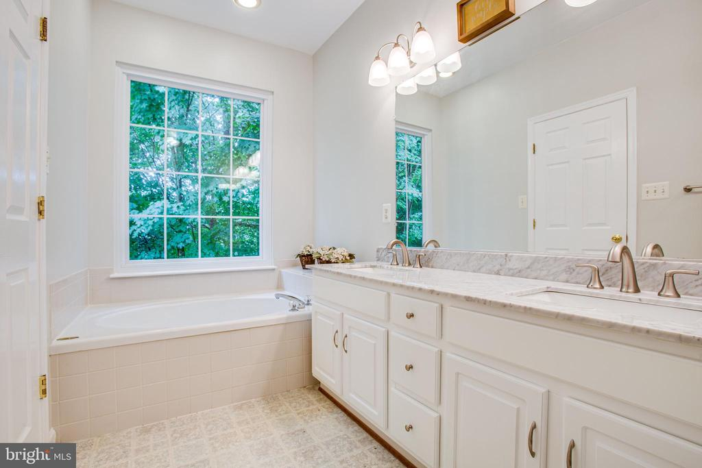 Soaking tub with large window overlooking trees - 8539 BERTSKY LN, LORTON