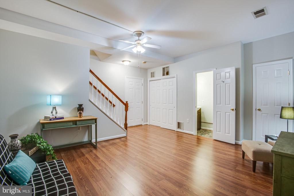 Stairs up, door to two-car garage, and half bath - 8539 BERTSKY LN, LORTON
