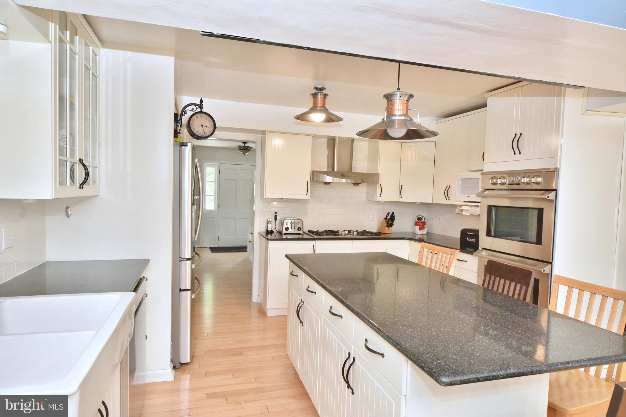 Stainless steel appliances and white cabinets..