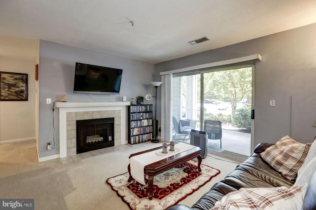 Living Room with Fireplace & Patio Access - 20313 BEECHWOOD TER #101, ASHBURN