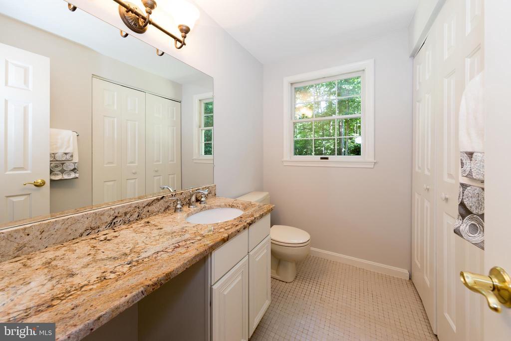 Main floor half bath has large storage closet too! - 7100 LAKETREE DR, FAIRFAX STATION