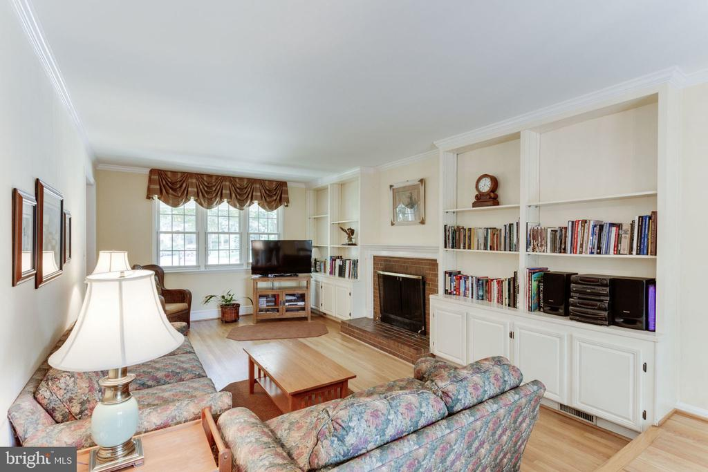 Family room with custom shelving, brick fireplace - 7710 FALSTAFF CT, MCLEAN